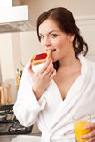Woman eating toast in kitchen Royalty Free Stock Photography