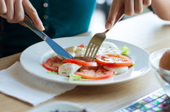 Woman eating tomato and mozzarella Royalty Free Stock Images
