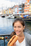 Woman eating traditional danish fast food hot dog Stock Photography