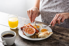 Woman eating a traditional English breakfast Royalty Free Stock Photo