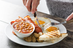Woman eating a traditional English breakfast Stock Images