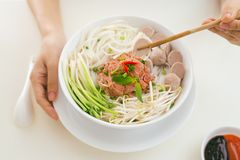 Woman eating traditional Vietnamese Pho noodle using chopsticks. Woman eating traditional Vietnamese Pho noodle using chopsticks royalty free stock image
