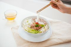 Woman eating traditional Vietnamese Pho noodle using chopsticks. Royalty Free Stock Photo
