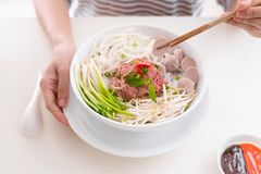 Woman eating traditional Vietnamese Pho noodle using chopsticks. Woman eating traditional Vietnamese Pho noodle using chopsticks royalty free stock images