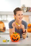 Woman eating trick or treat candy in halloween decorated kitchen. Halloween candy is so good! Happy young woman in decorated kitchen eating trick or treat candy Stock Photography