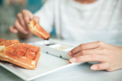 Woman eating waffle. Close up of woman holding a waffle and dip into sauce Stock Photos