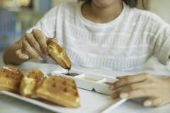 Woman eating waffle Stock Image