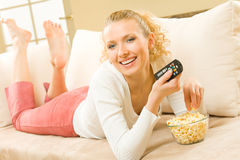 Woman eating and watching TV Stock Image