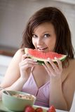 Woman eating watermelon. Young beautiful woman having a bite of watermelon royalty free stock image