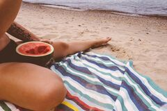 Woman eating watermelon on beach Royalty Free Stock Photos