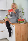 Woman is eating watermelon on the kitchen Royalty Free Stock Images
