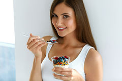 Woman Eating Yogurt, Berries And Oatmeal For Healthy Breakfast. Healthy Weight Loss Food. Portrait Of Pretty Smiling Fit Girl Having Yogurt, Berries And Oatmeal Stock Images