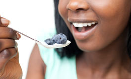 Woman eating a yogurt with blueberries. Close-up of a woman eating a yogurt with blueberries against a white background Royalty Free Stock Photography