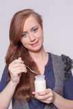 Woman eating a yogurt with a spoon Royalty Free Stock Images
