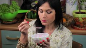 Woman eating yogurt and take cell phone stock video footage