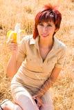 Woman eats a banana fruit. With calcium and potassium outdoors Stock Image