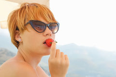 Woman eats berry. Woman eats strawberry on beach. Summer day Stock Image