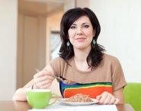 Woman eats buckwheat cereal Royalty Free Stock Photography