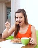 Woman eats buckwheat porridge Stock Image
