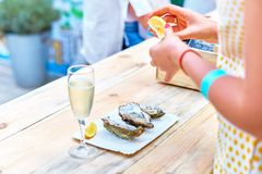 A woman eats fresh oysters on a plate. A woman eats fresh oysters. a wooden table, a plate with three oysters, salt, a woman`s hands, a glass of champagne, a Stock Images