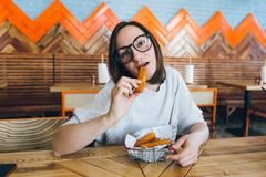 Woman eats fried cheese sticks in a cafe royalty free stock images