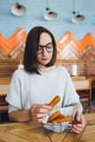 Woman eats fried cheese sticks in a cafe stock image