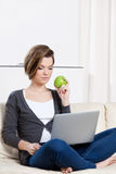 Woman eats a green apple surfing on the internet Royalty Free Stock Photography