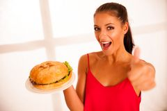 Woman eats hamburger isolated over white background Stock Photography