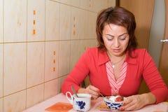 A woman eats an ice-cream. With a strawberry stock photos
