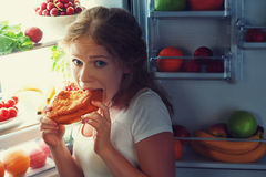 Woman eats night stole the refrigerator. Woman eats sweets at night to sneak in a refrigerator Royalty Free Stock Photography