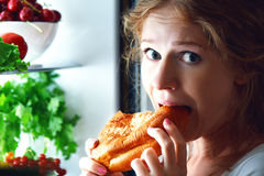 Woman eats night stole the refrigerator Stock Photos