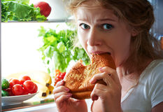Woman eats night stole the refrigerator Royalty Free Stock Images