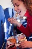 Woman eats pancake on airplane Royalty Free Stock Photo
