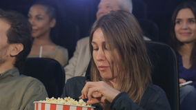 Woman eats popcorn at the movie theater. Middle aged woman eating popcorn at the movie theater. Middle aged woman sitting against background of two young women stock video