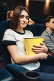 Woman eats popcorn while watching movie in cinema. Young women eats popcorn while watching movie in cinema. Showtime Royalty Free Stock Image