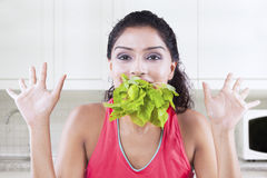 Woman eats raw spinach Stock Photo