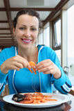 Woman eats shrimps and other seafood Stock Image