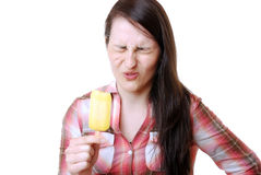 Woman eats a sour popsicle. Woman eats a sour fruit popsicle Stock Image