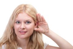 Woman eavesdropping with hand behind her ear Stock Images