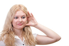 Woman eavesdropping with hand behind her ear Stock Image