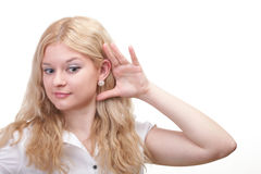 Woman eavesdropping with hand behind her ear Stock Photos