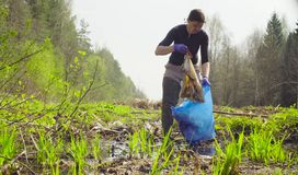 The woman ecologist collecting garbage Royalty Free Stock Images