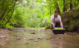 Woman ecologist opening a tool box and taking samples of water
