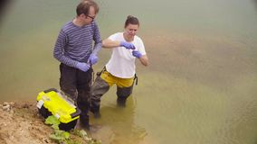 Woman ecologist taking samples of water. Man and woman scientist environmentalist standing in a river. Woman taking sample of water and pouring it into the test stock footage