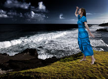 Woman on the edge of a breakaway over the storming sea Royalty Free Stock Images