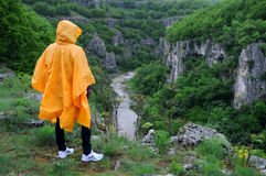 Woman on the Edge of the Canyon. A woman in orange rain poncho stands on the edge of Emen canyon in Bulgaria on a raw foggy morning in the spring Royalty Free Stock Images