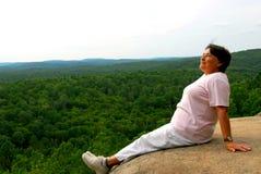 Woman edge cliff. Mature woman sitting on cliff edge enjoying scenery Stock Photography