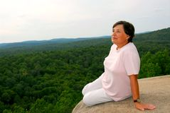 Woman edge cliff. Mature woman sitting on cliff edge enjoying scenery Stock Images