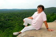 Woman edge cliff. Mature woman sitting on scenic cliff edge smiling Stock Image