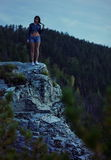 Woman on edge of cliff. Young woman on edge of cliff with forested mountainside in background royalty free stock images